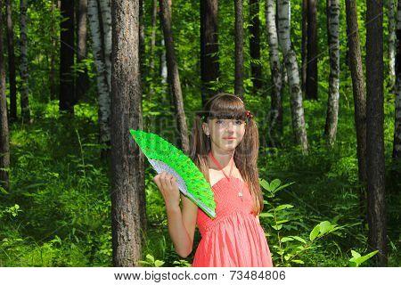 Girl fanning herself with green fan