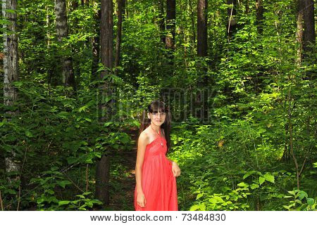 Girl in a red dress in the forest