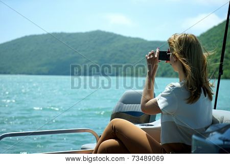 the girl on the boat photographs a landscape