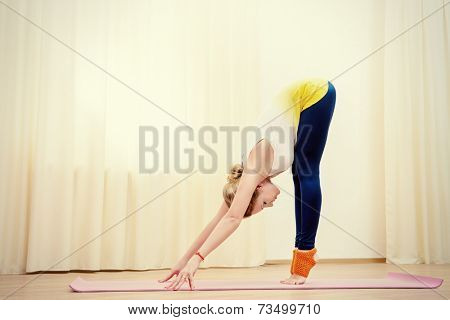 Slender athletic girl doing yoga exercises indoor. Stretching.
