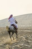 pic of saudi arabia  - An anonymous Arab man in traditional clothing riding his horse in the sand of a desert bathed in golden sunlight - JPG