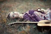 image of country girl  - Beautiful hippie girl with guitar lying on the grass - JPG
