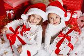foto of twin baby  - Santa hat Christmas girls holding christmas gifts smiling happy and excited - JPG