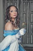picture of pompous  - Young beautiful medieval woman in long blue dress with mirror in the old room - JPG