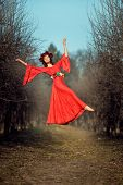 foto of habilis  - In the park among the trees levitating girl with a wreath of flowers on her head - JPG