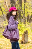 picture of knitted cap  - Young stylish woman dressed in oversized knitted sweater skinny jeans peaked cap with big bag in city park - JPG