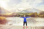 picture of pier a lake  - Senior woman is exercising on the pier by the tarn in beautiful mountains - JPG