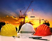 picture of engineering construction  - safety helmet on civil engineer working table against crane lifting meterial in building construction site - JPG