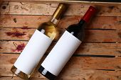 image of crate  - Bottles of red and white wine with blank labels in a wooden crate with grape juice stains - JPG
