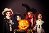 stock photo of witchcraft  - Cheerful children in halloween costumes posing with pumpkin over dark background - JPG