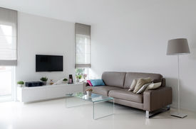 stock photo of taupe  - White living room with taupe leather sofa and glass table - JPG