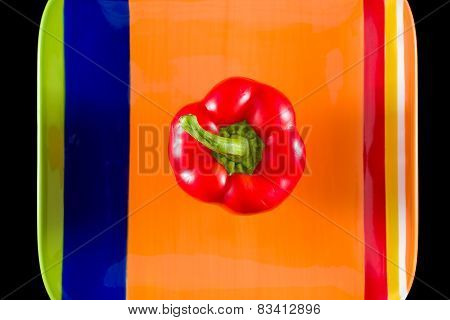 Red Bell Pepper Sitting On A Colorful Dish