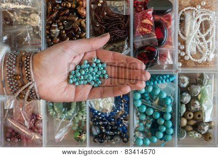 woman's hand holding sewing beads