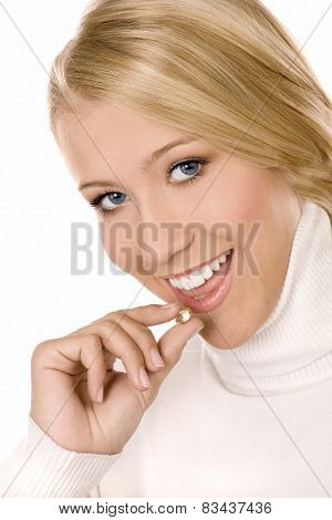 Smiling girl with pill isolated on white