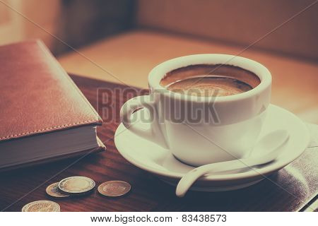 Vintage Stylized Photo Of Coffee Cup, Diary And Coins On Table In Cafe