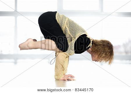 Sporty Female Standing In Yoga Crane Pose In Class