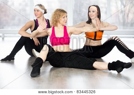 Group Of Three Females Doing Dynamic Fitness Exercises In Class