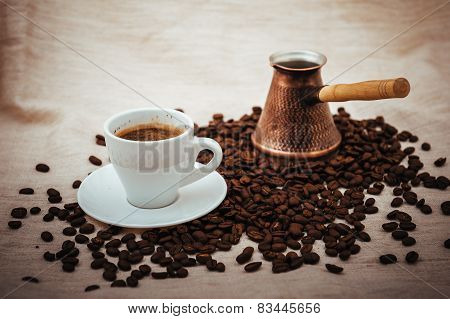 Coffee turk and cup of coffee on burlap background. coffee beans isolated on white background. roast