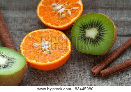 Fruit set - orange tangerine half,  kiwi and cinnamon sticks on hessian linen fabric cloth