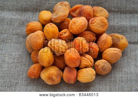 Heap of dried apricots on hessian linen fabric cloth