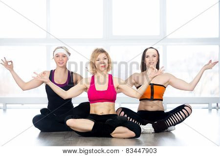 Group Of Three Females Practice Yoga In Class