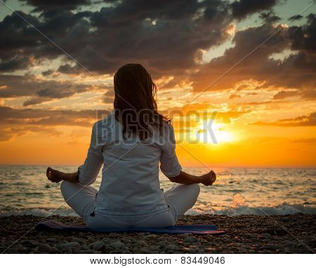 Woman Practicing Yoga by the Sea at Sunset