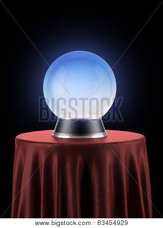 Magic globe on table covered with red cloth
