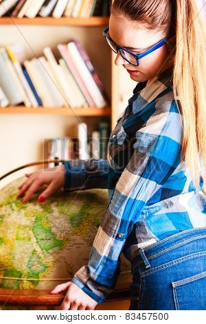 Girl In Library Pointing To Globe