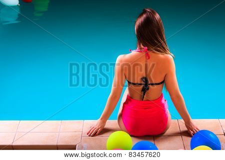Girl In Swimsuit Relaxing At Poolside Back View.