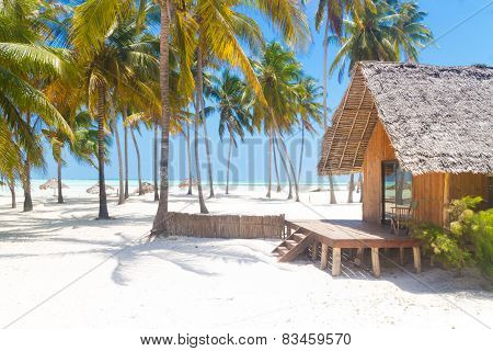 Wooden bungalow on tropical white sandy beach.