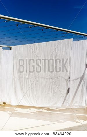 White Clothes Hanging On The Line Against Blue Sky.