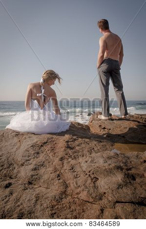 Young beautiful bridal couple having fun together on rock wall