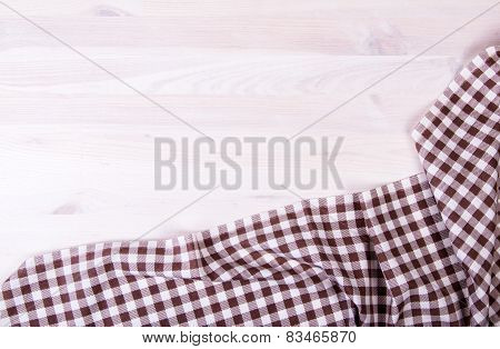Brown Folded Tablecloth Over Bleached Wooden Table