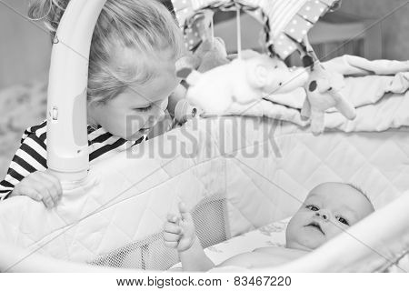 Happy Little Sister Looks Into The Cradle