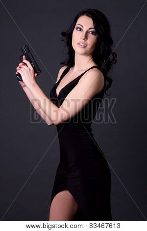 Young Sexy Woman Secret Agent Posing With Gun Over Grey