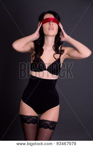 Young Beautiful Sexy Woman In Black Lingerie With Tied Eyes Over Grey