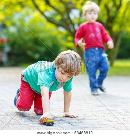 Two Little Kid Boys Playing With Car Toys
