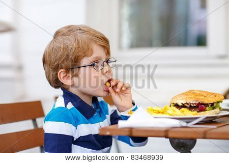Little Boy Eating Fast Food: French Fries And Hamburger