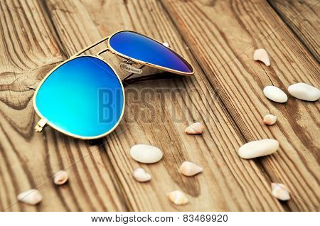Blue Mirrored Sunglasses And Shells On The Wooden Background Close Up
