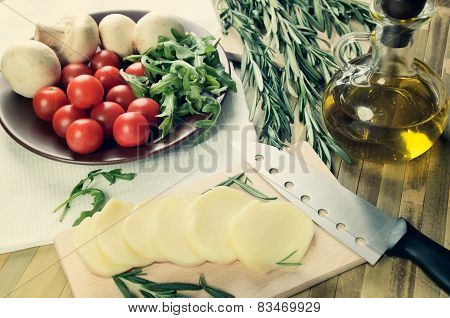 Tinted Image Cheese, Tomatoes And Herbs On A Kitchen Table Top View