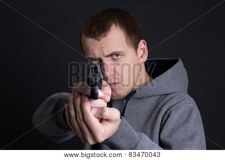 Man Criminal Aiming With Gun Over Grey