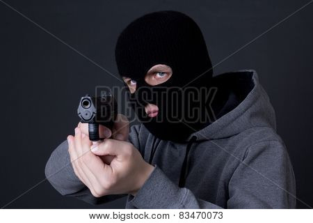Man Criminal In Black Mask Aiming With Gun Over Grey