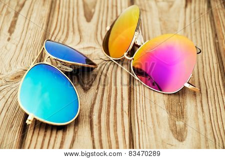 Two Colored Sunglasses Close Up On The Wooden Background