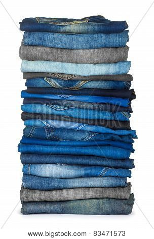 High Stack Of Various Shades Of Blue Jeans On A White Background