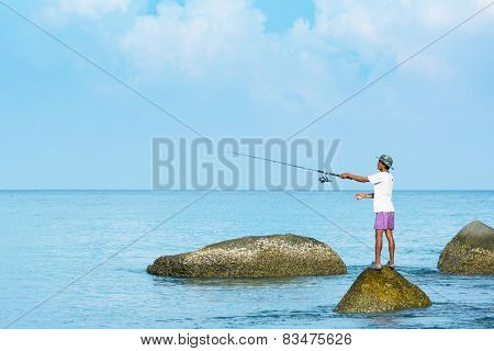 Phuket, Thailand - Circa Apr 2014: Thai Fisherman Casts With His Rod From A Precarious Standing Posi