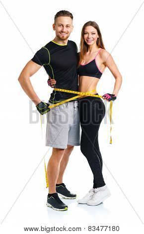 Happy Athletic Couple - Man And Woman With Measuring Tape On The White