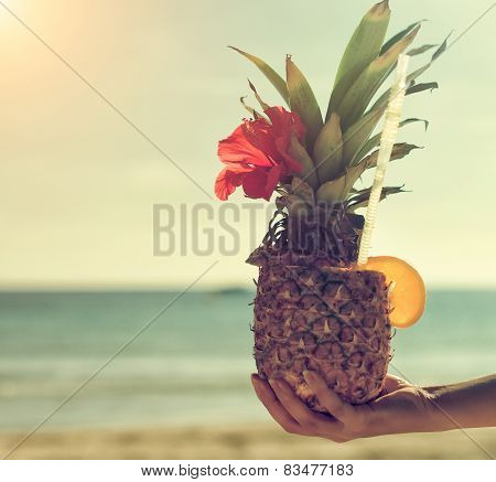 Woman's Hand Holding Exotic Pineapple Cocktail.