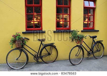 Two old bicycles and a yellow wall