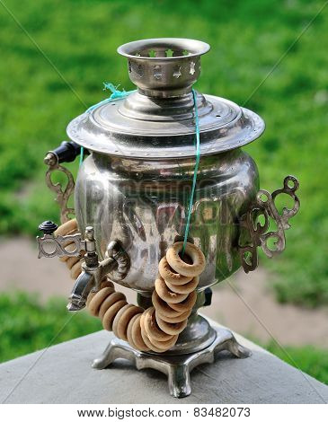 Old russian tea samovar with a bunch of bagels.