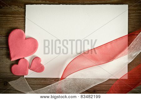 The Piece Of Paper Lying With Hearts And Ribbons On A Wooden Background